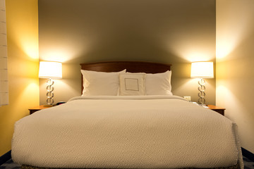 King sized bed in a luxury hotel room with illuminated lamp light