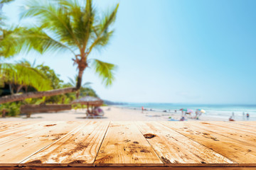 Top of wood table with seascape, palm tree, calm sea and sky at tropical beach background. Empty...