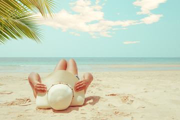 Leisure in summer - Young woman in straw hat lying sunbathe on a tropical beach. Memories of summer vacation concept. retro color tone. Wall mural