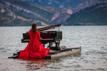 woman dressed in red playing the piano on a lake