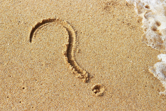Question mark drawn on golden sand top view, copy space