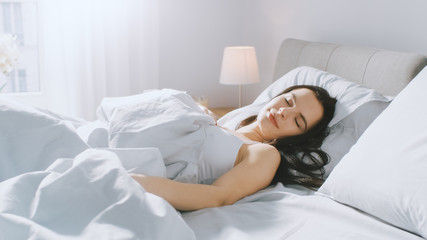 Attractive Brunette Cozily Sleeps in Her Bed while Early Morning Sunrays Illuminate Her. Warm, Cozy and Sweet Picture of Beauty Sleeping