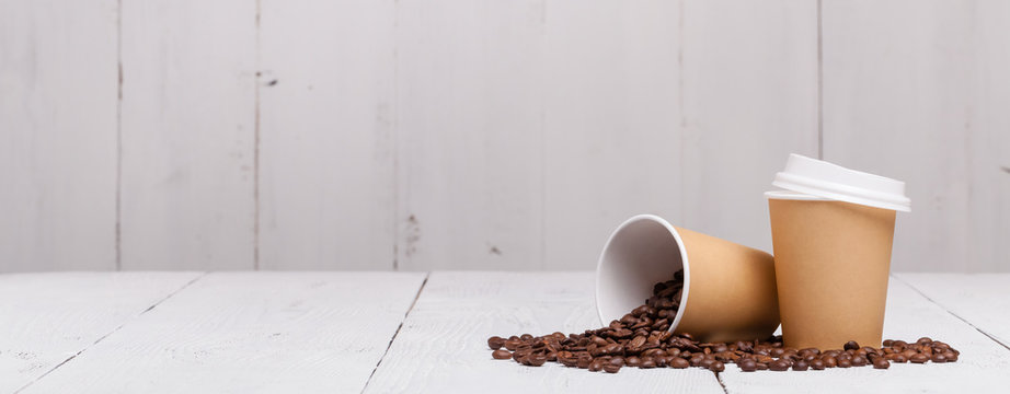 Paper cup of coffee and coffee beans on white wooden background