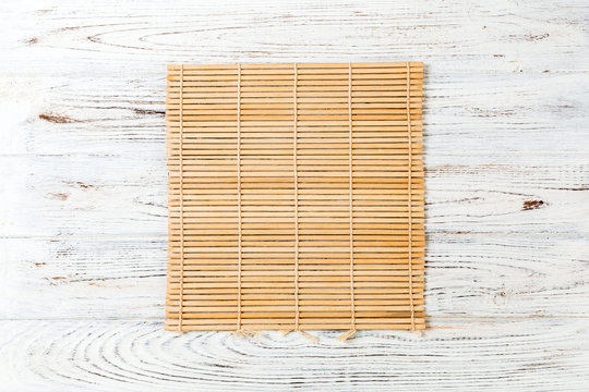 Empty Asian Food Background. brown Bamboo mat on wnite wooden background top view with copy space flat lay