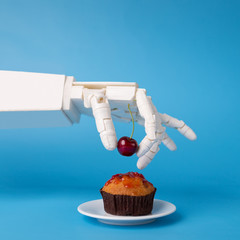 Robot hand decorating sweet cupcake with fresh cherry