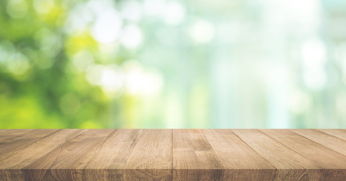 Real wood table top texture on blur leaf tree garden background.