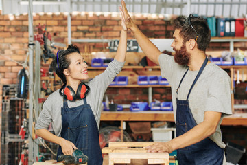 Happy young female carpenter giving high five to her coworker after finishing work