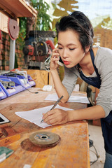 Serious young female carpenter accepting order of client by phone