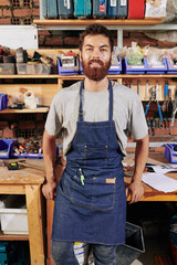 Cheerful bearded carpenter in denim apron leaning on table in his workshop and looking at camera
