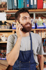 Portrait of young smiling carpenter calling on phone with client