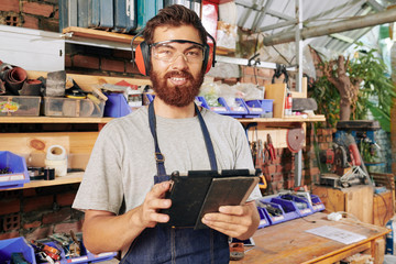 Portrait of smiling carpenter in protective goggles and ear muffs working on tablet computer