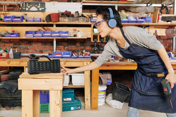 Smiling female carpenter tuning on speaker before starting to work with wood
