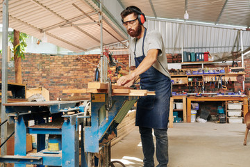 Serious Caucasian carpenter wearing ear muffs when cutting wooden plank on workbench with circular saw