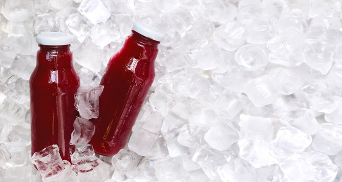 Red bottle with healthy smoothie on ice cubes background