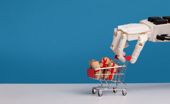 Robot hand holding shopping cart with gift boxes