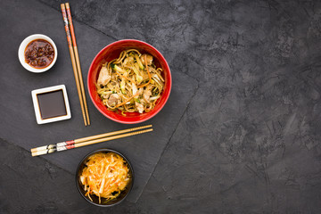 Salad; sauces and noodles served in bowl with chopsticks
