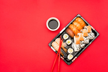Foto op Aluminium Sushi bar Sushi rolls and sashimi on tray with soy sauce over colored background