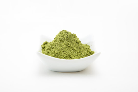 Healthy organic barley grass green powder isolated on white background. Barley grass powder for smoothies as health supplement for added vitamins and minerals to your diet. Young barley for cancer