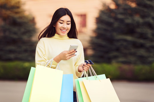 Girl walking with shopping bags and texting on phone