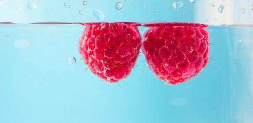 Beautiful raspberry in water with bubbles. Organic healthy food. Sweet berries. Summer harvest. Ripe raspberries isolated. Red berries background. Clean wet raspberry macro. Fototapete