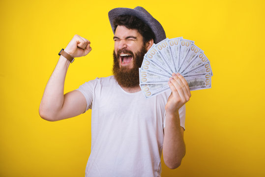 Photo of bearded guy,  standing overr yellow background, celebrating hi s triumph, holding a lot of money