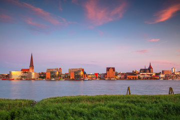 Fototapete - Rostock, Germany. Cityscape image of Rostock riverside with St. Peter's Church during summer sunset.