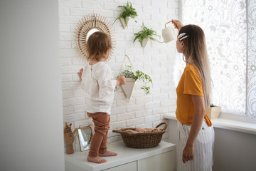 Mom and daughter watering flowers by the window