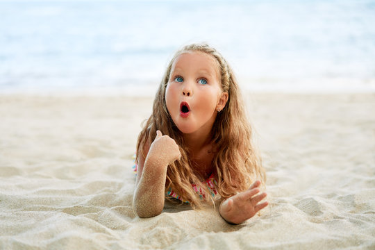 Surprised cute little blonde girl relax on the beach on summer holiday