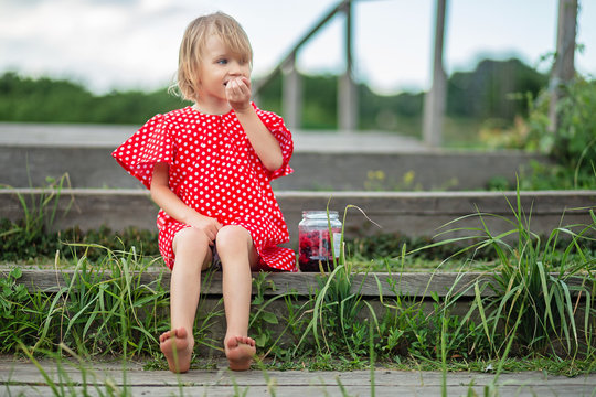 Little girl with glass jar of fresh berries. Blonde hair and blue eyes kid in polka dot red dress. Sitting on a wooden stairs enjoys a warm sunny day, eating raspberries and blackberry.