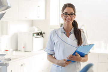 Portrait of female dentist .She standing in her dentist office. Wall mural
