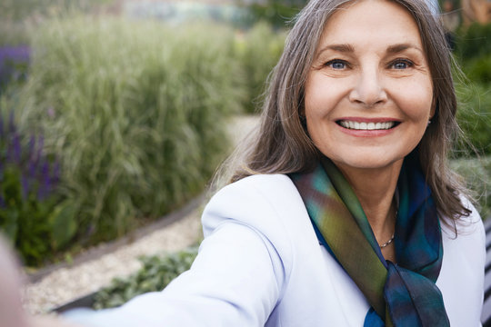 Summertime, people, age and leisure concept. Close up of beautiful blue eyed mature European lady in elegant clothes enjoying nice summer day outdoors, taking selfie using cell phone, smiling happily