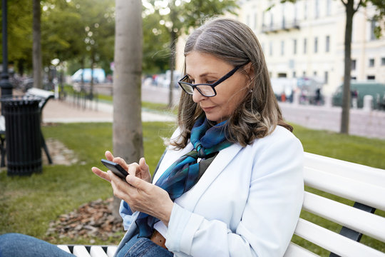Leisure, technology, business and modern lifestyle concept. Serious gray haired mature woman in stylish rectangular eyewear sitting on bench in park, using smart phone, messaging via online app