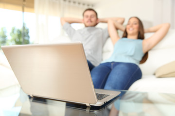 Couple watching online laptop content relaxed at home