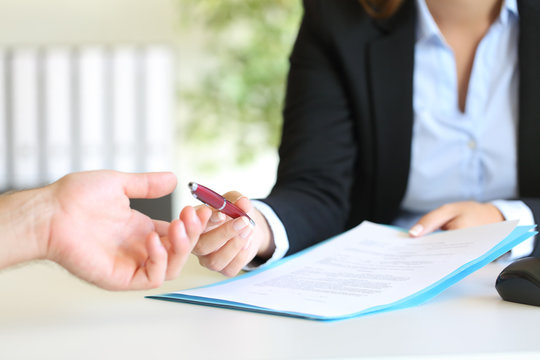 Dealer giving a pen to a client to sign a contract