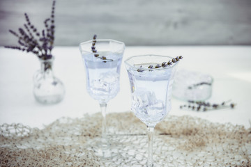 Fresh lavender lemonade with flowers and ice cubes in beautiful glasses on white wooden table. Detox water. Summer drink. Diet cocktail. Selective focus. Copy space.