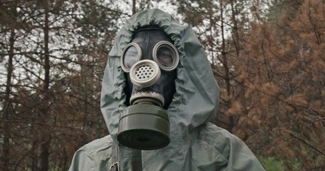 Man wearing a WWII Hazmat suit and gas mask carrying a counter in his hands as he scans for hazardous material in a forest