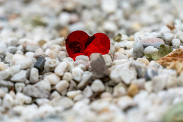 a shiny red heart lost on a path of white pebbles