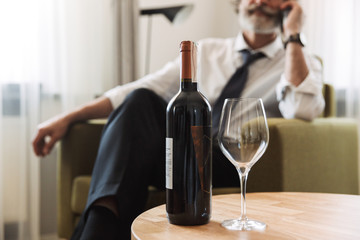 Image of attractive mature man talking on cellphone while sitting in bright apartment with bottle of wine