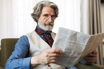 Portrait of bearded adult businessman reading newspaper while sitting on armchair in hotel apartment