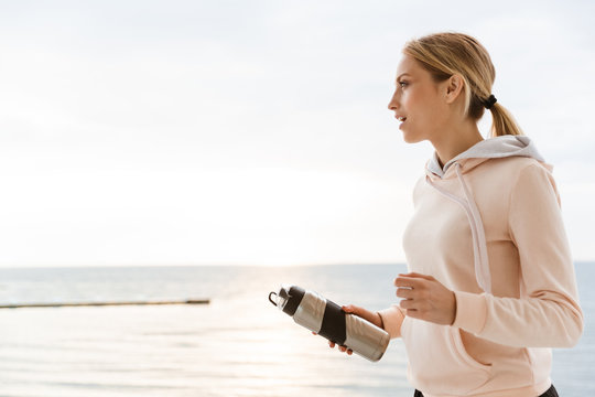 Image of blonde woman holding water bottle while working out on pier near seaside in morning