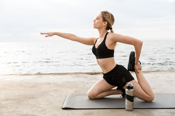Image of seductive woman doing exercise on mat with water bottle while working out near seaside in morning