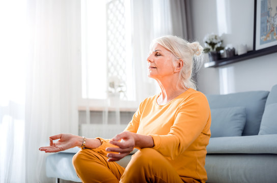 Senior female in lotus pose meditating sitting on floor at home