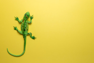 Green lizard toy on bright yellow background. Minimal art concept. Wall mural