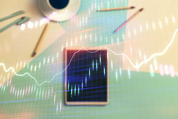 Double exposure of forex graph on digital tablet laying on table background. Concept of market analysis