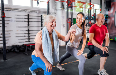 Personal trainer with senior couple doing rehab exercises at the gym Wall mural
