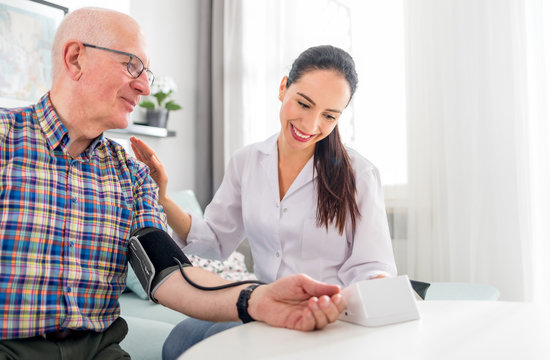 Nurse visiting senior male at home doing blood pressure measurement