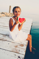 Young girl holding watermelon sitting on the wooden bridge. Summer beach holiday refreshing light food.