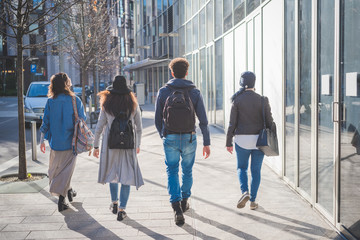 young people walking in modern metropolis and showing the back