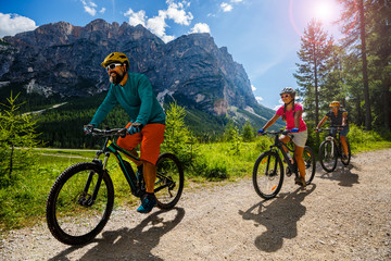 Wall Mural - Mountain biking woman and young girl along river in Dolomites, Italy