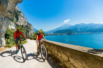 Cycling woman and man riding on bikes at sunrise mountains and Garda lake landscape. Couple cycling MTB enduro flow sentiero ponale trail track. Outdoor sport activity.